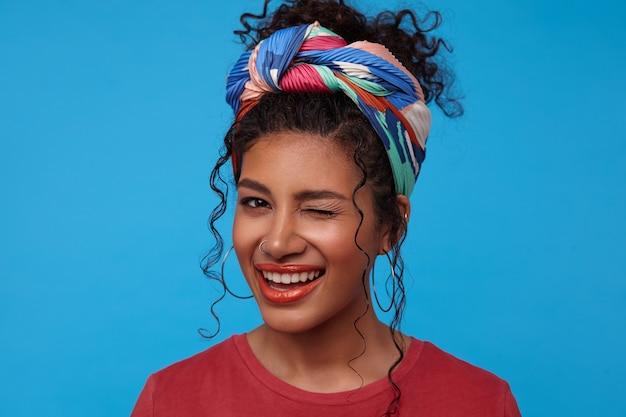 Freudige junge attraktive brünette lockige frau mit festlichem make-up zwinkert fröhlich vorne, während sie fröhlich lächelt und über blauer wand in farbigen kleidern steht