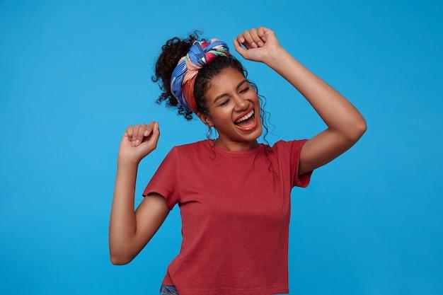 Freudige junge attraktive brünette lockige frau mit mehrfarbigem stirnband, das fröhlich singt und tanzt, während sie über der blauen wand mit erhobenen händen steht
