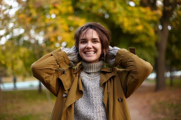 Freudige junge attraktive kurzhaarige brünette dame mit bob-frisur, die erhobene hände hinter ihrem kopf hält und freudig lächelt, während sie über vergilbte bäume im stadtpark geht
