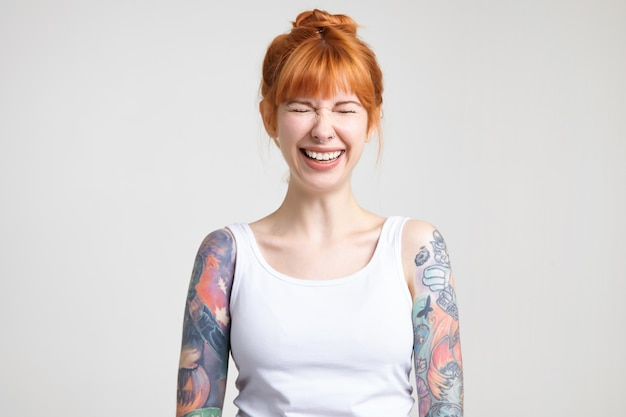 Freudige junge attraktive rothaarige frau mit tätowierungen, die ihre augen geschlossen halten, während sie fröhlich lachen, gekleidet in weißes hemd, während über weißem hintergrund posierend