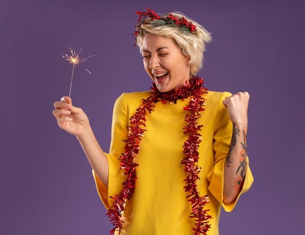 Freudige junge blonde frau, die weihnachtskopfkranz und lametta-girlande um den hals hält, die feiertagswunderkerze hält, die ja geste mit geschlossenen augen tut, die auf lila wand lokalisiert werden