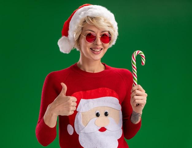 Freudige junge blonde frau, die weihnachtsmütze und weihnachtsmann-weihnachtspullover des weihnachtsmanns mit der brille trägt, die kamera hält, die weihnachtszuckerrohr zeigt daumen oben auf grünem hintergrund