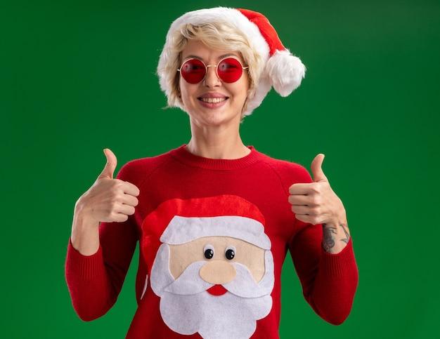 Freudige junge blonde frau, die weihnachtsmütze und weihnachtsmannpullover des weihnachtsmanns mit brille trägt, die kamera betrachtet, die daumen oben auf grünem hintergrund zeigt