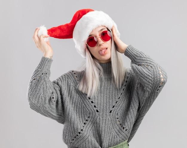 Freudige junge blonde frau im winterpullover und in der weihnachtsmannmütze, die spaß haben, zunge herauszustecken