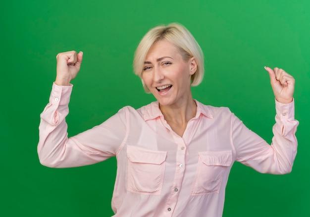 Freudige junge blonde slawische frau, die fäuste erhebt, die ja geste lokalisiert auf grünem hintergrund tun