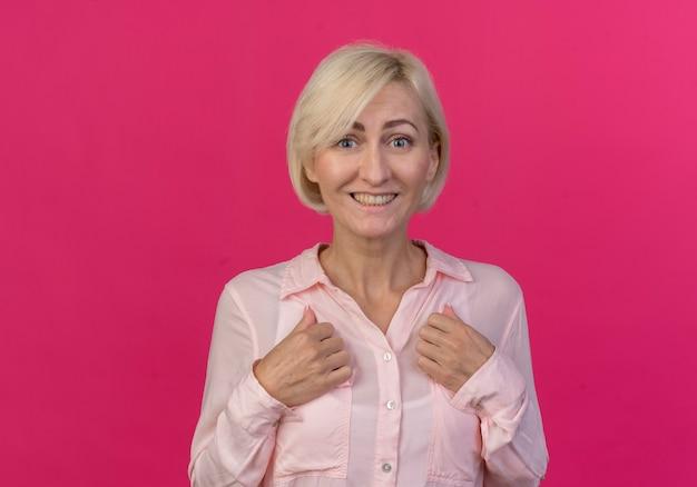 Freudige junge blonde slawische frau, die hände auf brust setzt und kamera lokalisiert auf rosa hintergrund mit kopienraum betrachtet