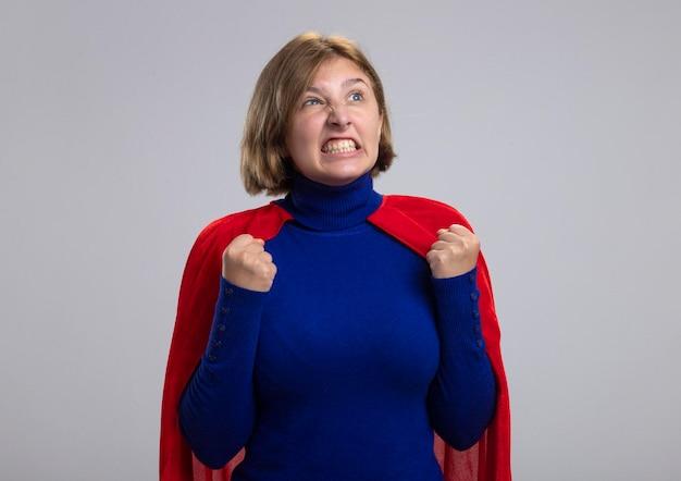 Freudige junge blonde superheldenfrau im roten umhang, der seite betrachtet, die ja geste lokalisiert auf weißer wand mit kopienraum tut