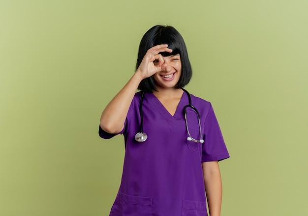 Freudige junge brünette ärztin in uniform mit stethoskop schaut durch finger lokalisiert auf olivgrünem hintergrund mit kopienraum