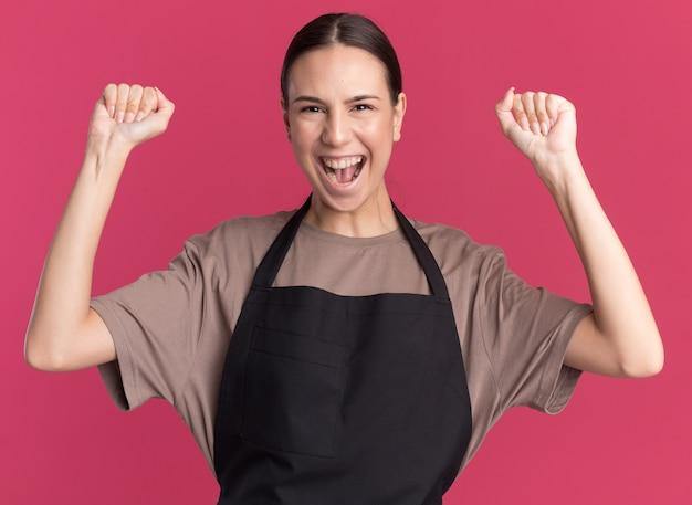 Freudige junge brünette friseurin in uniform steht mit erhobenen fäusten isoliert auf rosa wand mit kopierraum