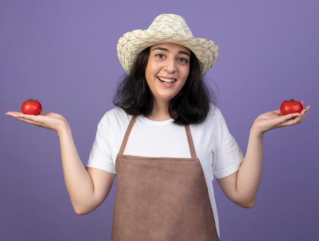 Freudige junge brünette weibliche gärtnerin in uniform, die gartenhut trägt, hält tomaten lokalisiert auf lila wand