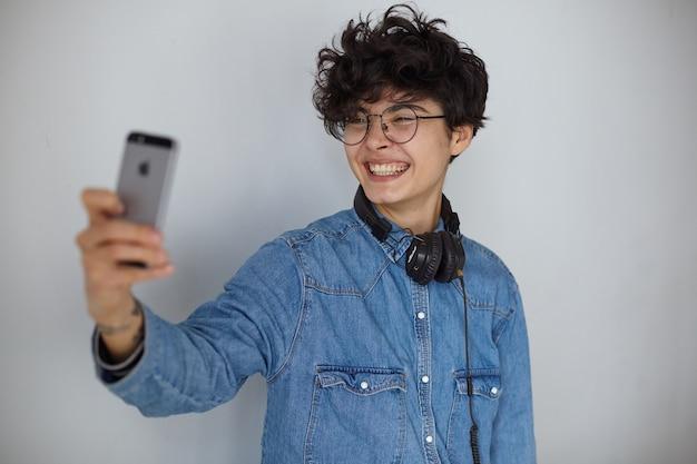 Freudige junge charmante kurzhaarige lockige frau, die kopfhörer an ihrem hals trägt, während sie über weißem hintergrund steht und breit in die kamera lächelt, während sie selfie mit ihrem smartphone macht