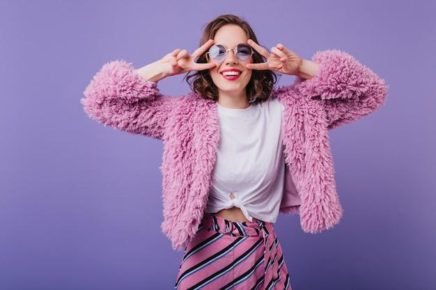 Freudige junge dame im flauschigen mantel lustiges tanzen auf lila wand. innenporträt der sinnlichen weißen frau mit dem wellenförmigen haar lachend