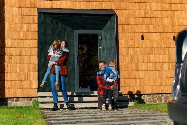 Freudige junge eltern treffen sich und umarmen ihre schönen kinder auf der veranda des hauses. glückliche familie