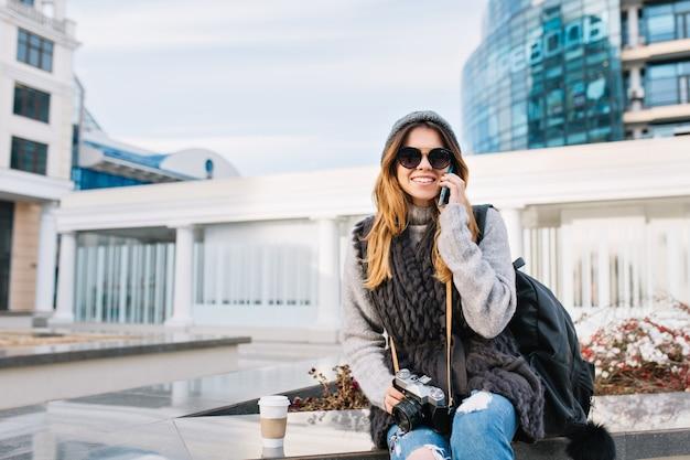 Freudige junge frau der stilvollen stadt, die im modernen stadtzentrum europas sitzt und winterwollpullover, sonnenbrille, strickmütze trägt. am telefon sprechen, mit tasche, kamera reisen, lächeln. platz für text.