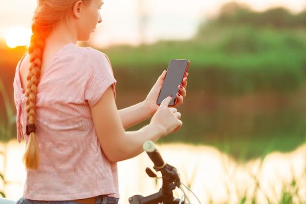 Freudige junge frau, die fahrrad am flussufer und auf der wiesenpromenade reitet