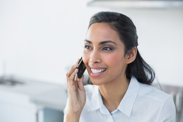 Freudige junge frau, die mit ihrem smartphone anruft