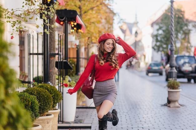 Freudige junge frau in der roten baskenmütze, die auf pflaster mit charmantem lächeln tanzt