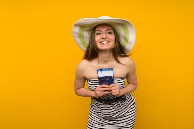 Freudige junge frau in einem strohhut und einem gestreiften kleid hält flugtickets mit einem pass auf einem gelben hintergrund.
