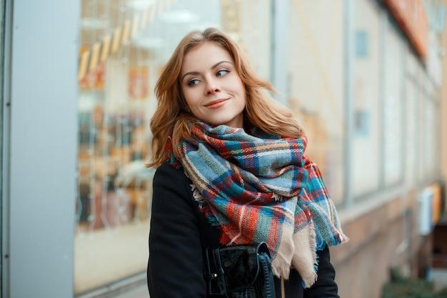 Freudige junge frau in einem warmen schwarzen wintermantel mit einer lederhandtasche mit einem modischen warmen wollschal in einem käfig steht in der nähe eines schaufensters in einer stadt, die mit festlichen lichtern geschmückt ist. glückliches mädchen