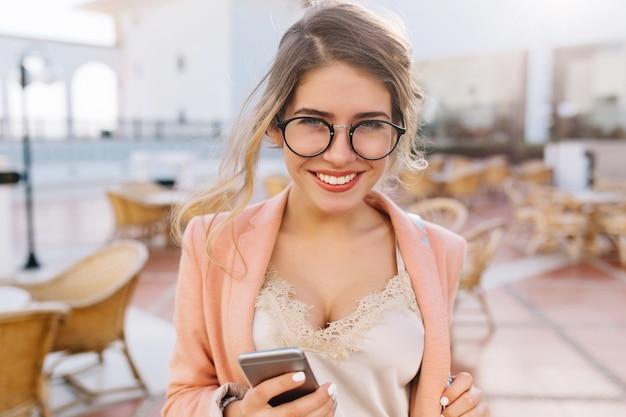 Freudige junge frau mit dem schönen lächeln, das graues smartphone in der hand hält, student, geschäftsdame. strassencafe. tragen sie eine stilvolle brille, eine rosa jacke und eine beige spitzenbluse.