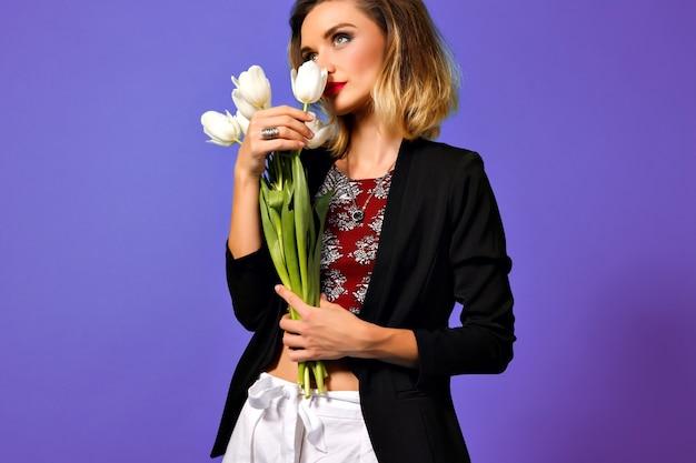 Freudige junge frau mit dem strauß der weißen tulpen, die zur seite lokalisiert auf lila hintergrund lächeln.