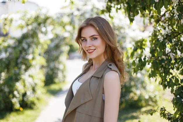 Freudige junge frau mit einem schönen lächeln in einer modischen sommerweste in einem stilvollen t-shirt steht