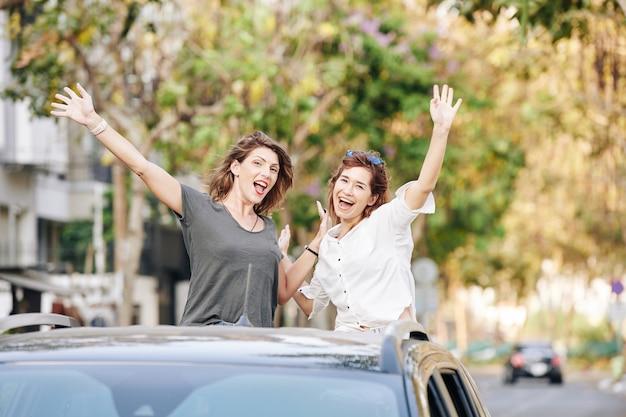 Freudige junge frauen, die im autokofferraum stehen