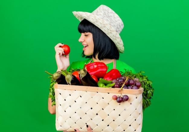 Freudige junge gärtnerin in uniform mit gartenhut hält gemüsekorb und schaut auf tomate