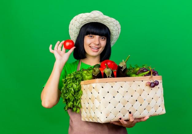 Freudige junge gärtnerin in uniform mit gartenhut hält gemüsekorb und tomate