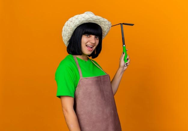 Freudige junge gärtnerin in uniform mit gartenhut hält hacke rechen
