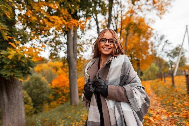 Freudige junge hipsterfrau in einem modischen gestrickten schal in stilvollen gläsern in einem trendigen mantel, der in einem park außerhalb der stadt aufwirft. fröhliches mädchenmodell mit einem positiven lächeln geht in den wald. herbst.