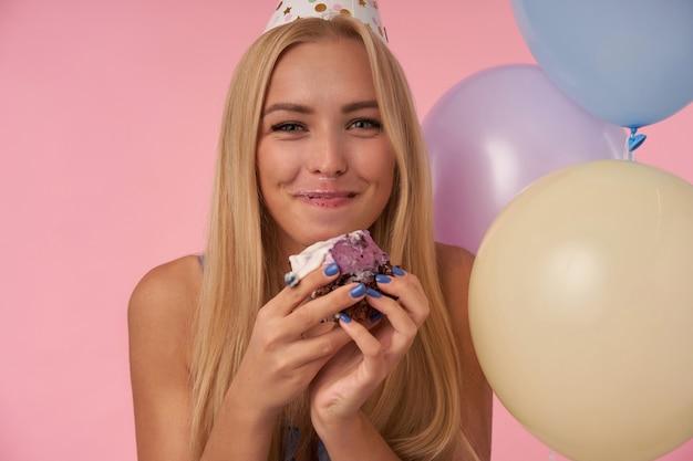 Freudige junge hübsche blonde frau, die in mehrfarbigen luftballons mit mund voller feiertagstorte aufwirft, glücklich zur kamera schaut und breit lächelt und ihre angenehmen gefühle über rosa hintergrund zeigt
