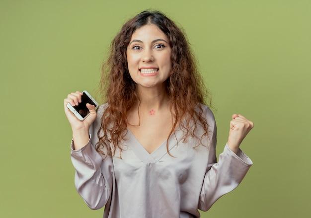 Freudige junge hübsche büroangestellte, die telefon hält und ja geste zeigt