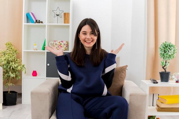 Freudige junge hübsche kaukasische frau, die auf sessel in entworfenem wohnzimmer sitzt und leere hände zeigt