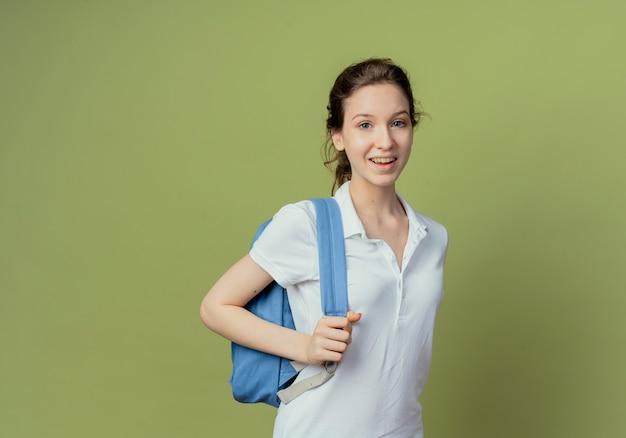 Freudige junge hübsche studentin, die rückentasche trägt und gurt der tasche lokalisiert auf olivgrünem hintergrund mit kopienraum hält
