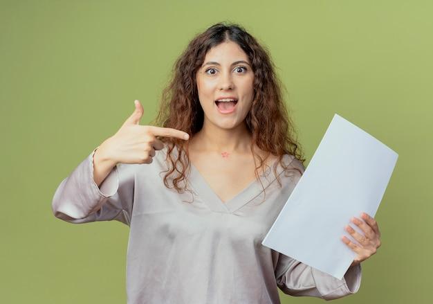 Freudige junge hübsche weibliche büroangestellte halten und zeigt auf papiere