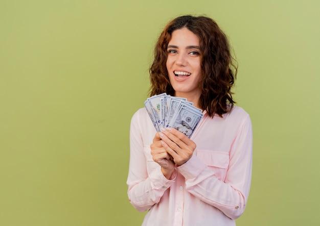 Freudige junge kaukasische frau hält geld, das kamera lokalisiert auf grünem hintergrund mit kopienraum betrachtet