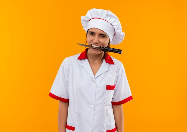 Freudige junge köchin, die kochuniform hält messer im mund auf isolierter gelber wand mit kopienraum trägt