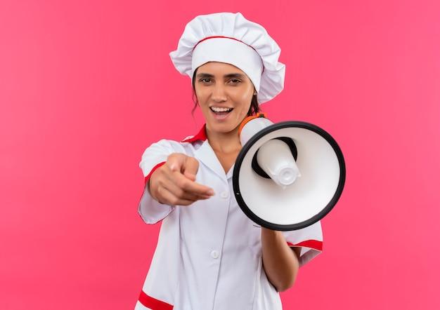 Freudige junge köchin, die kochuniform trägt, die lautsprecher hält, der sie geste auf isolierter rosa wand mit kopienraum zeigt