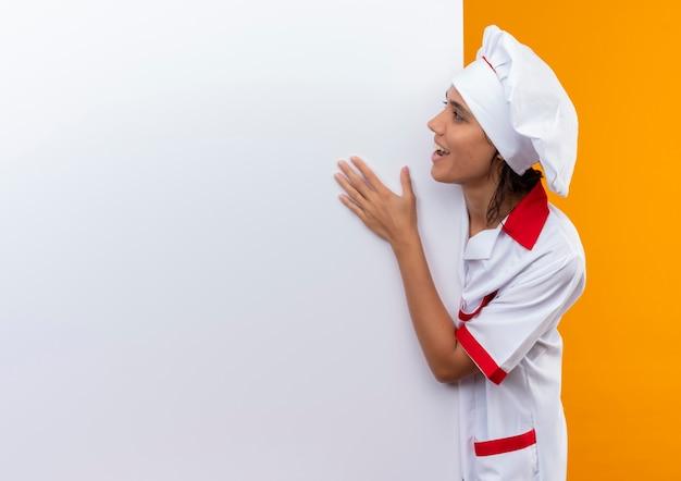 Freudige junge köchin, die kochuniform trägt, die weiße wand auf isolierter gelber wand mit kopienraum hält und betrachtet