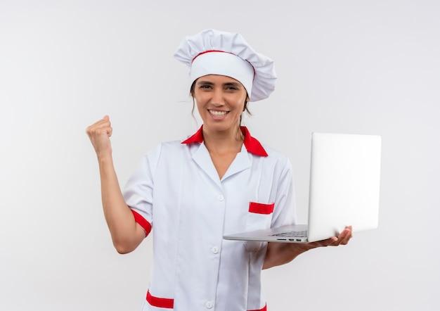Freudige junge köchin, die kochuniform trägt laptop hält und ja-geste auf isolierter weißer wand mit kopienraum zeigt