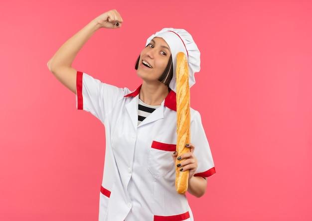 Freudige junge köchin in der kochuniform, die brotstab hält, der stark auf rosa gestikuliert
