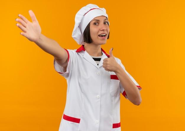 Freudige junge köchin in der kochuniform, die daumen oben zeigt und hand vorne auf orange lokalisiert ausdehnt