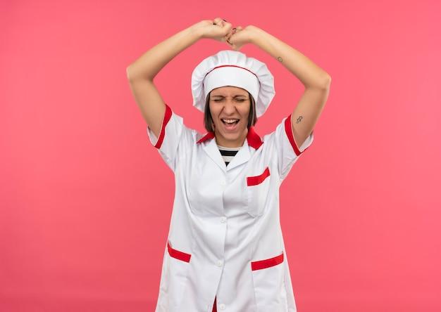 Freudige junge köchin in der kochuniform, die fäuste mit geschlossenen augen auf rosa lokalisiert