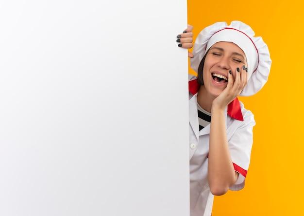 Freudige junge köchin in der kochuniform, die hinter weißer wand steht, die hand auf wange mit geschlossenen augen lokalisiert auf orange setzt