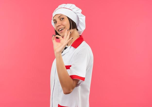 Freudige junge köchin in der kochuniform, die in der profilansicht steht und ok zeichen lokalisiert auf rosa tut