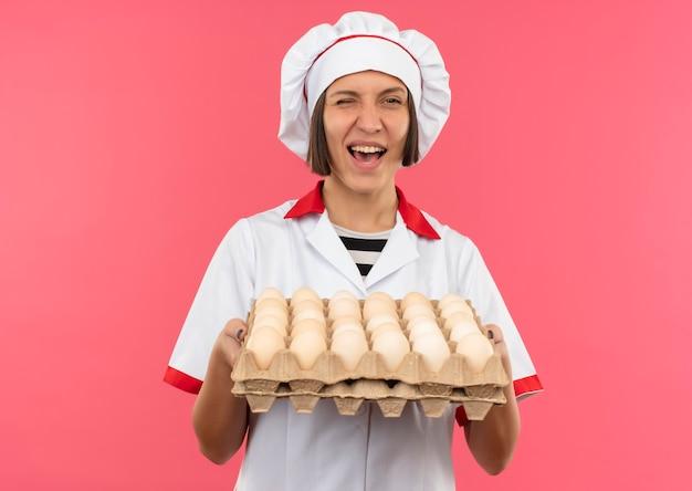 Freudige junge köchin in der kochuniform, die karton der eier hält und auf rosa lokalisiert zwinkert