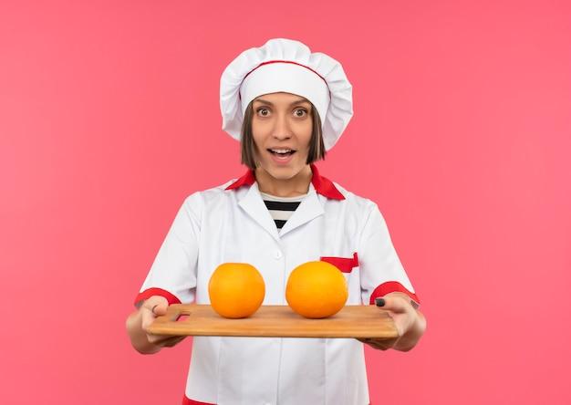 Freudige junge köchin in der kochuniform, die schneidebrett mit orangen darauf streckt, lokalisiert auf rosa