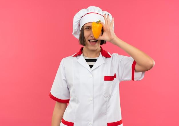 Freudige junge köchin in der kochuniform, die vorne von hinten pfeffer lokalisiert auf rosa betrachtet