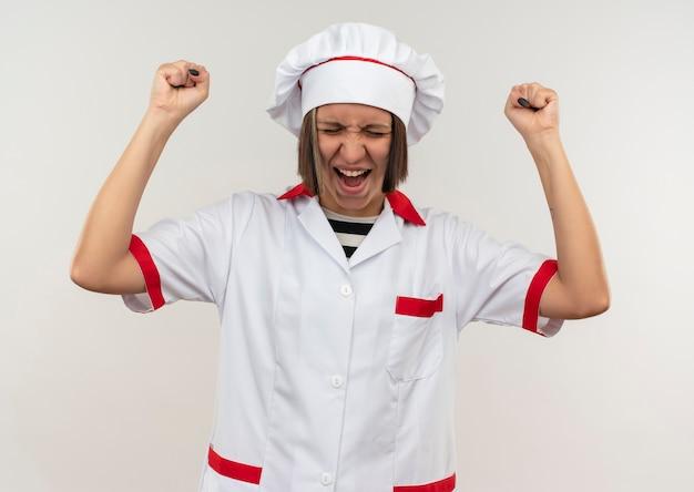 Freudige junge köchin in kochuniform, die fäuste mit geschlossenen augen auf weiß lokalisiert
